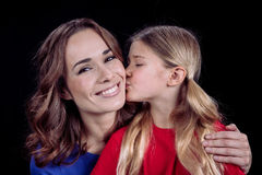 Daughter kissing happy mother royalty free stock image