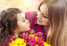 Daughter kissing happy mother with flowers. Mother`s day concept. Family holiday Royalty Free Stock Photos