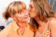 Daughter is kissing her mother Stock Image