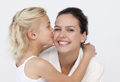 Daughter kissing her mother in bathroom Royalty Free Stock Image