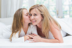 Daughter kissing her mother on the cheek in the bed Royalty Free Stock Image