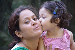 Daughter kissing her mother. On cheek. Outdoors.  Mother's day, family, childhood and people concept Stock Image