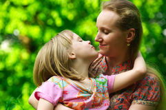 Daughter kissing her mum. Little daughter kissing her mum stock photography