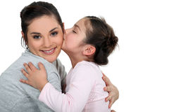 Daughter kissing her mum Royalty Free Stock Photography