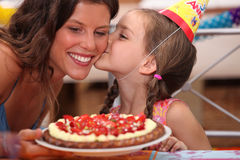 Daughter kissing mommy. At birthday party Royalty Free Stock Photos