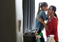 Daughter kissing mommy at home Stock Image