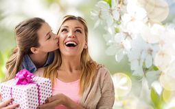 Daughter kissing mother and giving her present Royalty Free Stock Photography