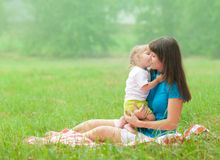 Daughter kissing mother with love. Outdoor Royalty Free Stock Image