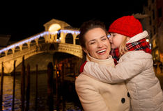 Daughter kissing mother near Rialto Bridge in Christmas Venice Stock Images