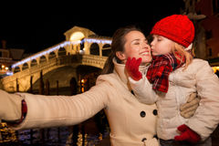 Daughter kissing mother taking selfie in Christmas Venice, Italy Royalty Free Stock Image