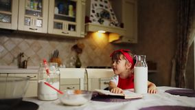 Daughter in the kitchen in a red apron read the recipe cake in a notebook. Daughter in the kitchen in a red apron read the recipe cake in a notebook stock video footage