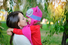 Daughter in a knitted cap with his mother in the park Stock Photos