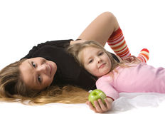 Daughter lies on mum on the floor royalty free stock photos