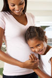 Daughter Listening To Pregnant Mother's Stomach royalty free stock images