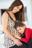Daughter Listening To Pregnant Mother's Stomach. Smiling Stock Image