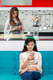 Daughter looking at smartphone white mother cooking in kitchen Royalty Free Stock Images