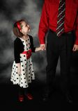Daughter looking up to her daddy. Little girl holding her daddy's hand looking up at him adoringly, wearing red and black polka dot dress Stock Photography