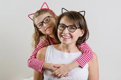 Daughter lovingly embraces her mother. Parent and child in glasses. The daughter lovingly embraces her mother. Parent and child in glasses stock photography