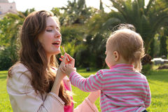 Daughter makes up with lipstick to the mom. Happy loving family. sunny spring day in the park royalty free stock photography