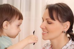 Daughter making up her mother Royalty Free Stock Photos