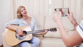 Daughter making a video with her mother playing on an acoustic guitar. Daughter making a video with her mother playin on an acoustic guitar. Making an amateur stock footage