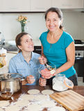 Daughter with mature mother cooking meat dumplings Stock Photos