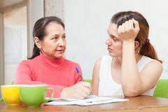 Daughter with mature mother  fills in the documents Stock Photos