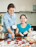 Daughter with mature  mother making perogies with berries Stock Photos