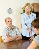 Daughter and mature parents having serious talking. In home interior royalty free stock photos