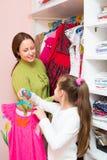 Daughter and mom choosing apparel Stock Image