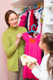 Daughter and mom choosing apparel Stock Images