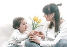 Daughter Mom gives flowers stock photo
