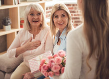 Daughter, mom and granny. Cute teenage girl is giving flowers and a gift box to her beautiful granny and mother while those are sitting on couch and smiling royalty free stock photography
