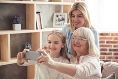 Daughter, mom and granny. Three generations of women. Beautiful granny, mother and daughter are doing selfie and smiling while sitting on couch at home Royalty Free Stock Photo