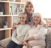 Daughter, mom and granny. Three generations of women. Beautiful granny, mother and daughter are hugging, looking at camera and smiling while sitting on couch at royalty free stock images