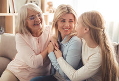 Daughter, mom and granny. Three generations of women. Beautiful granny, mother and daughter are hugging, talking and smiling while sitting on couch at home royalty free stock photo