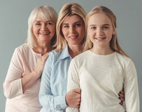 Daughter, mom and granny. Three generations of women. Beautiful granny, mother and daughter are looking at camera and smiling, on gray background Royalty Free Stock Images