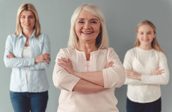 Daughter, mom and granny. Three generations of women. Beautiful granny, mother and daughter are looking at camera and smiling, standing with crossed arms on gray stock photography
