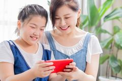 Daughter and mom play mobile game stock photos