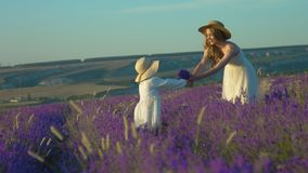 Daughter and mom send each other air kisses in the flowering field of lavender stock footage