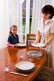 Daughter and mom setting the table Stock Image