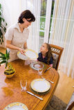 Daughter and mom setting the table Stock Images