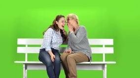 Daughter and mom are sitting on a bench. Green screen. Daughter and mom are sitting on a bench and talking on talking on various topics. Green screen stock video