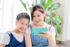 Daughter and mom use smartphone stock photography