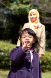 Daughter and Mother. A little girl showing her finger to show 'peace' sign while her mother watching at the back at the garden Stock Photo