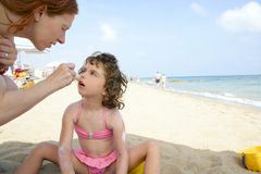 Daughter and mother on beach sun screen moisture. Daughter and mother on the beach sun screen protection moisture cream Stock Photography