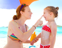 Daughter and mother in beach with sunscreen. In bikini Royalty Free Stock Image