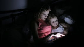 Daughter and mother in bed. Playing game on touch pad stock video footage
