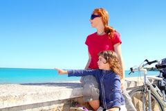 Daughter and mother on bicycle in beach Royalty Free Stock Photos