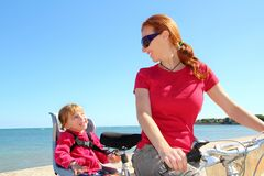 Daughter and mother on bicycle in beach sea Royalty Free Stock Photo